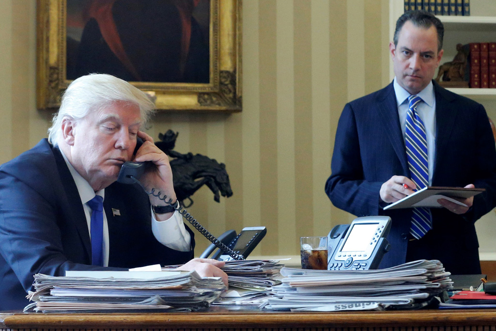 U.S. President Donald Trump, flanked by Chief of Staff Reince Priebus (R), speaks by phone with Russia's President Vladimir Putin in the Oval Office at the White House in Washington, U.S. January 28, 2017. REUTERS/Jonathan Ernst - RTSXT9A
